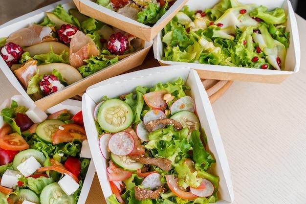 Grüne natursalate in öko-thermobox mit microgreen, kalb, gurke, tomate, käse. sicherheitslieferung bei quarantäne covid 19.