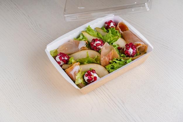 Grüne natursalate in öko-thermobox mit prosciutto, microgreen, granat, schale, käse. sicherheitslieferung bei quarantäne covid 19.