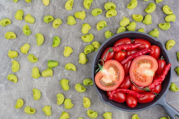 Grüne nudeln mit roten chilischoten und tomaten in einer schwarzen pfanne.