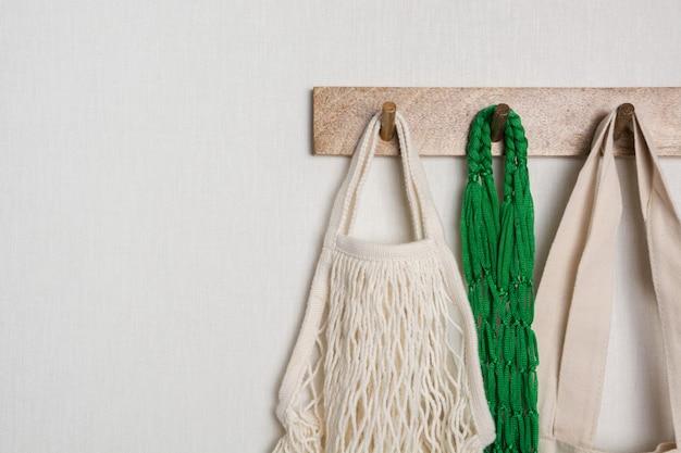 Grüne öko-taschen aus baumwolle und mesh hängen am kleiderbügel an der wand. bereit zum einkaufen.