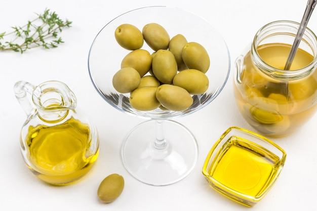 Grüne olive auf brotscheibe. glas oliven. ölflasche. draufsicht