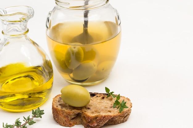 Grüne olive auf brotscheibe. glas oliven. ölflasche .. kopierraum