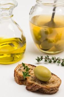 Grüne olive auf brotscheibe. glas oliven. ölflasche. nahansicht
