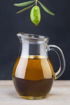 Grüne olive und glas olivenöl auf holzuntergrund