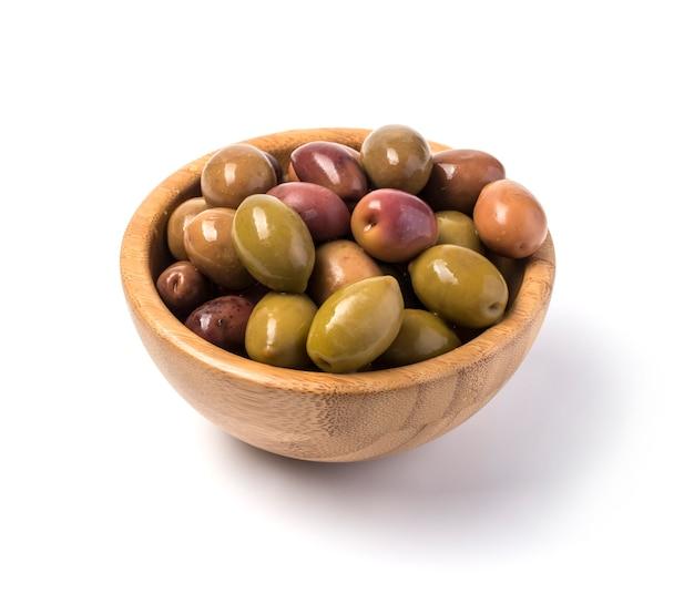 Grüne oliven an der holzschale lokalisiert auf weiß