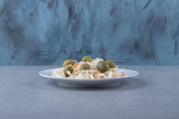 Grüne oliven auf dem sauerkraut auf dem teller, auf dem marmorhintergrund.