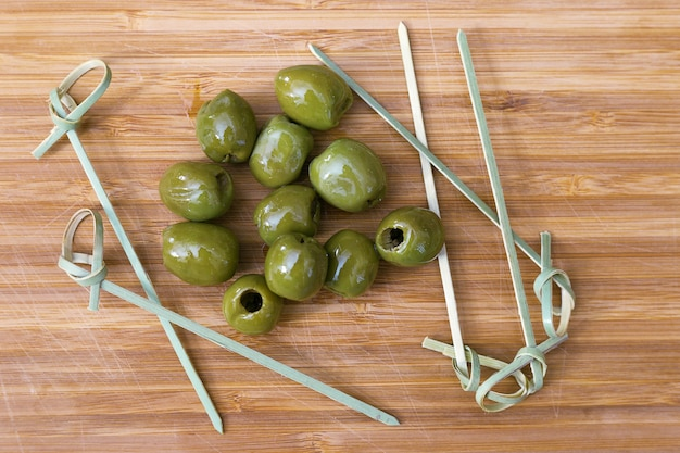 Grüne oliven auf holz,