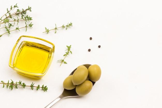 Grüne oliven im löffel. olivenöl in glasschüssel. flache lage ..