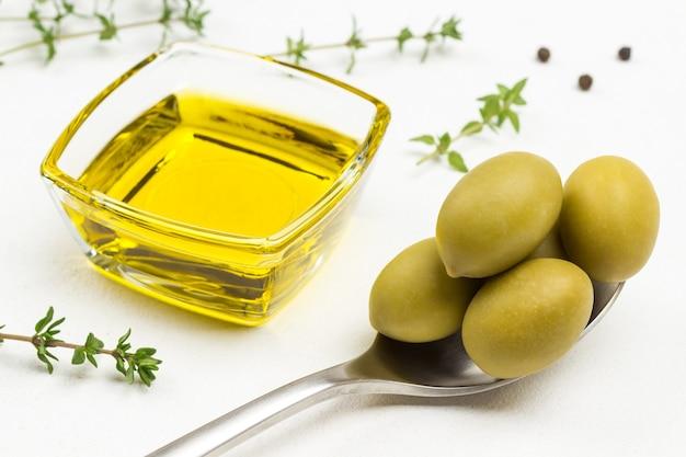 Grüne oliven im metalllöffel. olivenöl im glas. nahaufnahme