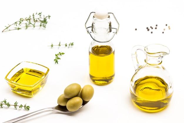 Grüne oliven im metalllöffel. olivenöl im glas. thymianzweige. draufsicht.