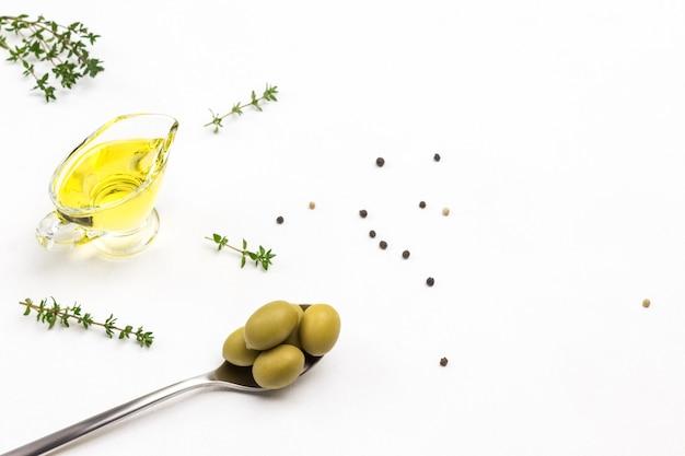 Grüne oliven im metalllöffel. olivenöl im glas. thymianzweige. speicherplatz kopieren. weißer hintergrund. draufsicht.