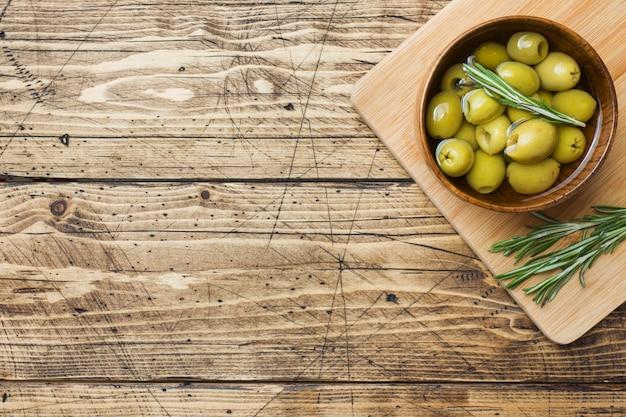 Grüne oliven in den hölzernen schüsseln auf holztisch