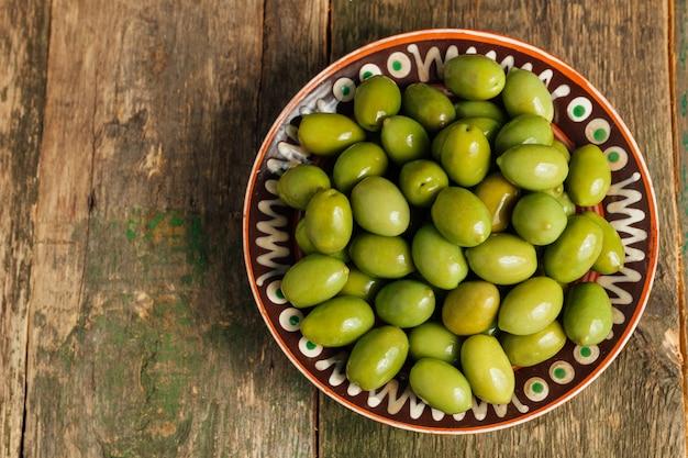 Grüne oliven in der braunen schüssel