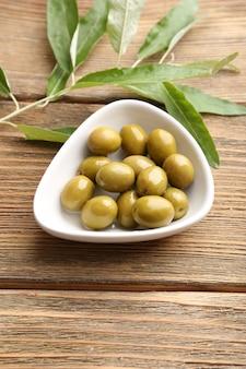 Grüne oliven in der schüssel mit blättern auf dem tisch