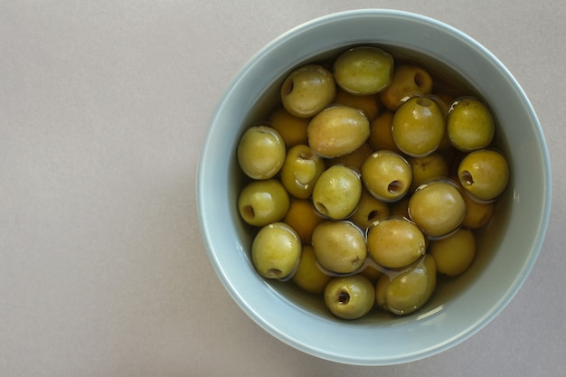 Grüne oliven in einer grauen platte auf einem grauen hintergrund. mediterrane küche.