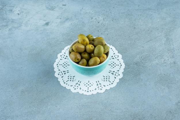 Grüne oliven in einer schüssel auf einem untersetzer, auf dem marmortisch.