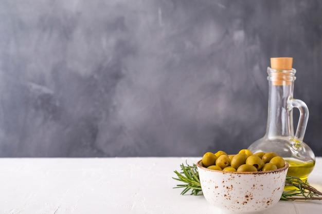 Grüne oliven in einer schüssel und olivenöl auf weißem hintergrund. kopierraum, textraum