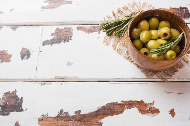 Grüne oliven in holzschalen auf holztisch. draufsicht mit platz für text.