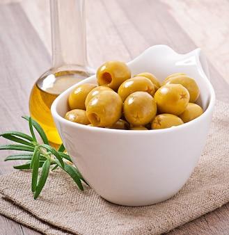 Grüne oliven in schüssel.