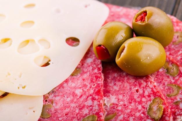 Grüne oliven liegen auf geschnittenem schweizer käse und salami