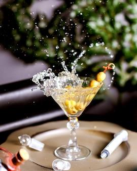 Grüne oliven spritzten in alkoholische getränke