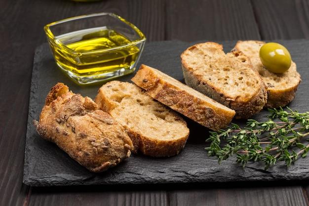 Grüne oliven und brotscheiben. olivenöl in glas und thymianzweigen. draufsicht