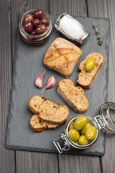 Grüne oliven und brotscheiben. olivenöl in glas und thymianzweigen. flach liegen