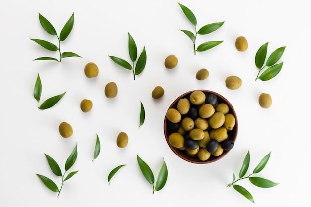 Grüne oliven und schwarzer pfeffer in einer draufsicht der schüssel
