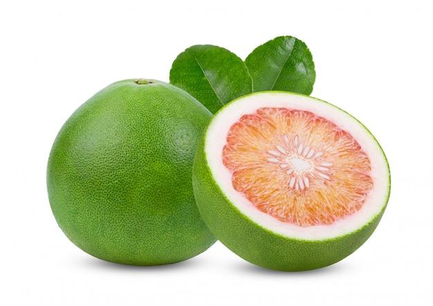 Grüne pampelmuse zitrusfrucht mit blättern auf weißem tisch.