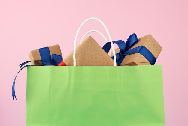 Grüne papiertüte mit einer geschenkbox