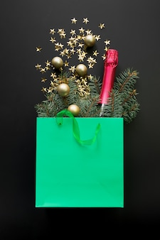 Grüne papiertüte mit weihnachtsgeschenken, sekt, roten kugeln und glänzenden goldenen schneeflocken auf schwarzraum einkaufen