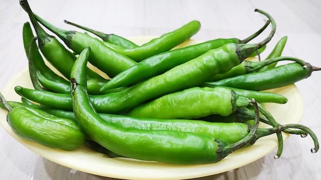 Grüne paprika im dreschkorb auf holztisch in indien