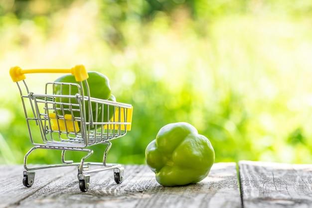 Grüne paprika in einem kleinen einkaufswagen.