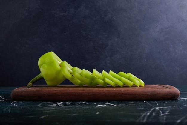 Grüne paprika-scheiben auf holzbrett.