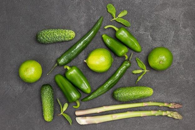 Grüne paprika, spargel, gurken und limetten auf dem tisch. schwarzer hintergrund. flach legen
