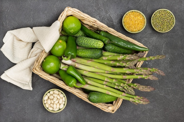 Grüne paprika, spargel, gurken und limetten im rattankorb. beige serviette auf korb. bulgur und mungobohnen in schalen. schwarzer hintergrund. flach legen
