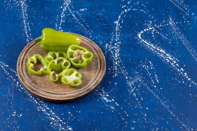 Grüne paprika und scheiben auf holzbrett auf marmoroberfläche.