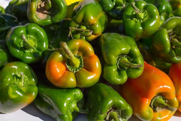 Grüne paprikas in einer reihe am markt gestapelt