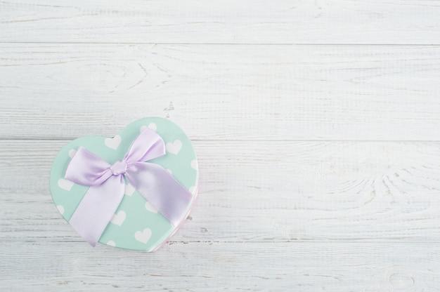 Grüne pastellgeschenkbox und rosa bogen