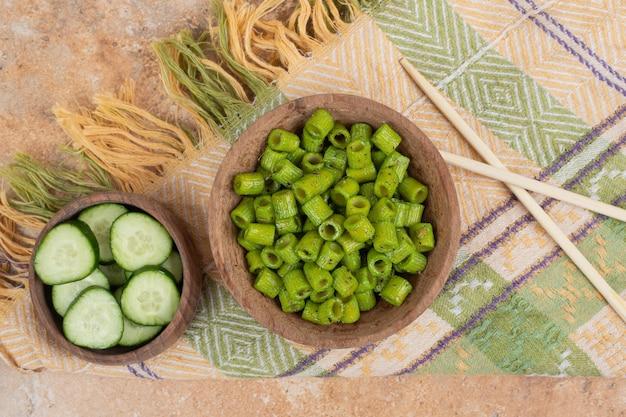 Grüne penne-nudeln mit gurkenscheiben auf tischdecke.
