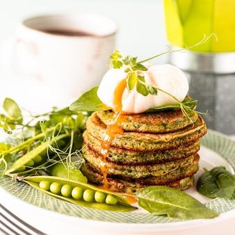 Grüne pfannkuchen mit spinat und pochiertem ei. leckeres gesundes europäisches frühstück.