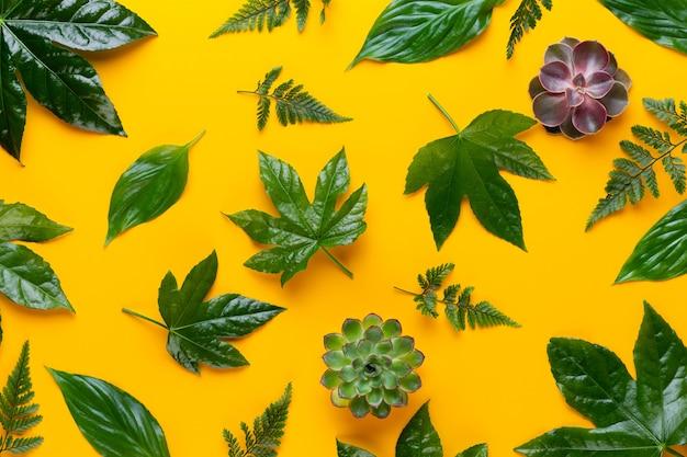 Grüne pflanzenblätter auf dem gelben hintergrund. retro vintage stil.