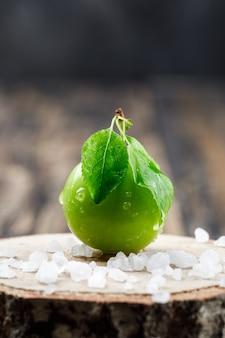 Grüne pflaume mit blättern und salzkristallen auf hölzerner und hölzerner stückwand, seitenansicht.