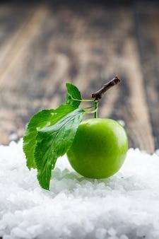 Grüne pflaume mit blättern und salzkristallen auf holzwand, seitenansicht.
