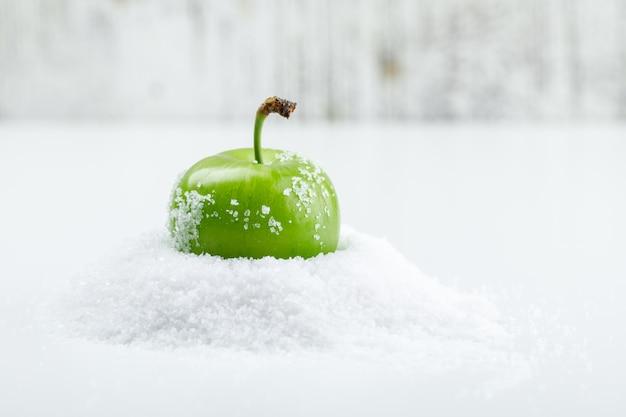 Grüne pflaume mit salzkristallen auf weißer und schmuddeliger wand, seitenansicht.