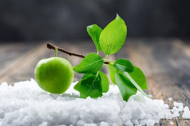 Grüne pflaume mit zweig und salzkristallen auf hölzerner und schmuddeliger wand, seitenansicht.
