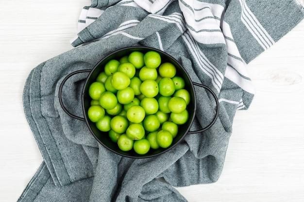 Grüne pflaumen in einem schwarzen topf auf küchentuch und weißem holz. draufsicht.