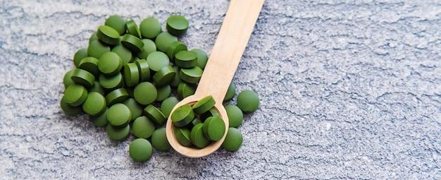 Grüne pillen von chlorella und spirulina. selektiver fokus-getränk