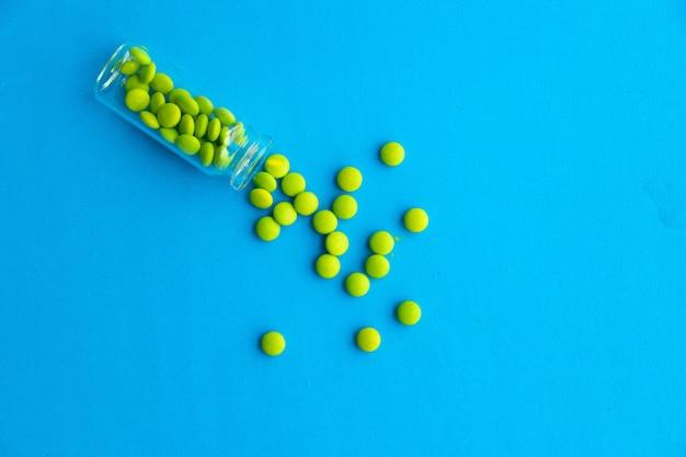 Grüne pillen von spirulina oder chlorella auf graublauem gipshintergrund in einer glasschüssel und in einem holzlöffel. gesundes superfood-diät- und detox-ernährungskonzept.