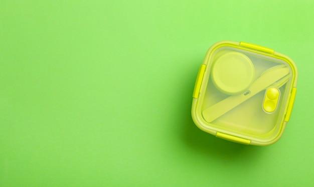 Grüne plastik-brotdose auf grünem hintergrund. draufsicht, flache lage. lebensmittelbehälter für schule und büro.